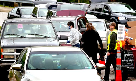 Volunteer Brooke Bensinger, center, and others bring food to cars which are routed through a parking lot at Red Lion High School during a pop-up drive-thru food distribution Wednesday, May 20, 2020. The event was sponsored by the York County Food Bank and Community REACH, a Red Lion-based community aid organization. Bill Kalina photo