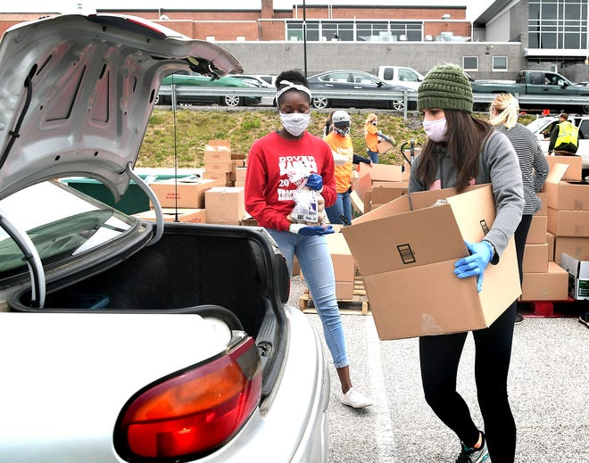 Volunteers Leah Bowers of Stewartstown and Chelsea Eziee, 17, of Dover, load food during a pop-up drive-thru food distribution at Red Lion High School Wednesday, May 20, 2020. The event was sponsored by the York County Food Bank and Community REACH, a Red Lion-based community aid organization. Bill Kalina photo