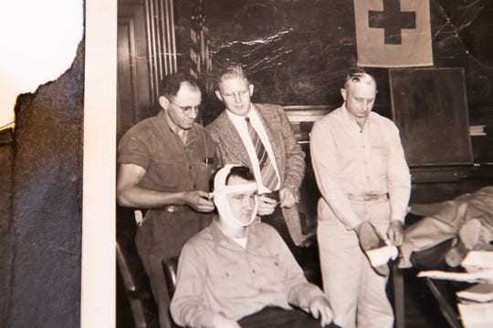 A photograph shows Dale Chapman (far left, standing) participating in a first-aid training session during his basic training in the U.S. Army in the 1940s.