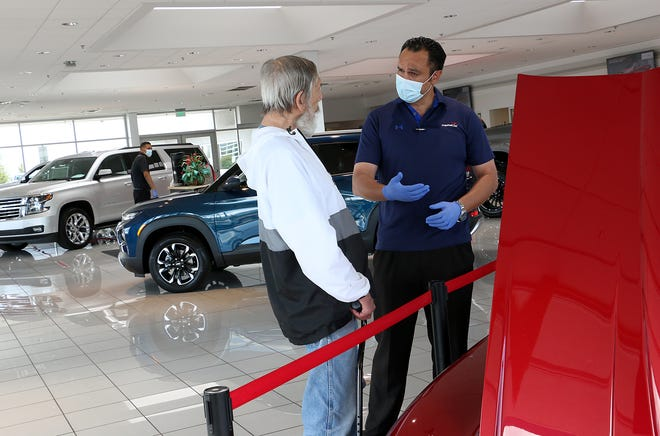 Salesman Zack Gaskins, right, helps out a customer at Champion Chevrolet in Reno on May 20, 2020.