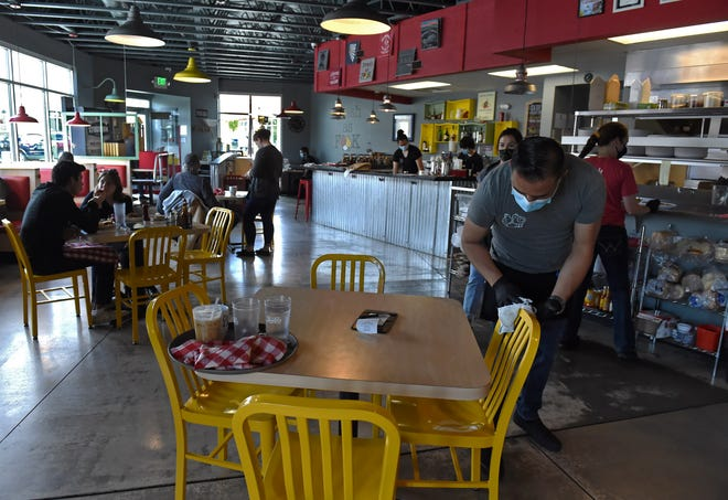 Two Chicks Restaurant employee Carlos Cuevas cleans a table and chairs after customers have eaten at the Midtown area restaurant in Reno, Nevada on May 20, 2020. The restaurant has opened for dining-in with new guidelines, such as distancing, closed bar area, condiments off the tables and enhanced cleaning.