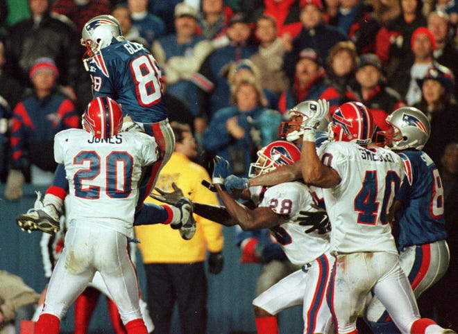 New England Patriots wide receiver Terry Glenn (88) is hit by Buffalo Bills saftey Henry Jones (20) as Glenn goes up for a Drew Bledsoe pass in the end zone as time runs out.