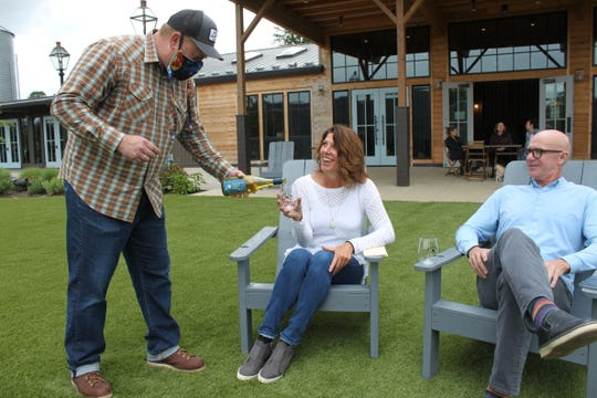 Manager Jeff Mathews pours wine for Stephanie Darrow of Vancouver, Washington, at Abbey Road Farm in Carlton. Abbey Road reopened on Saturday, May 16.