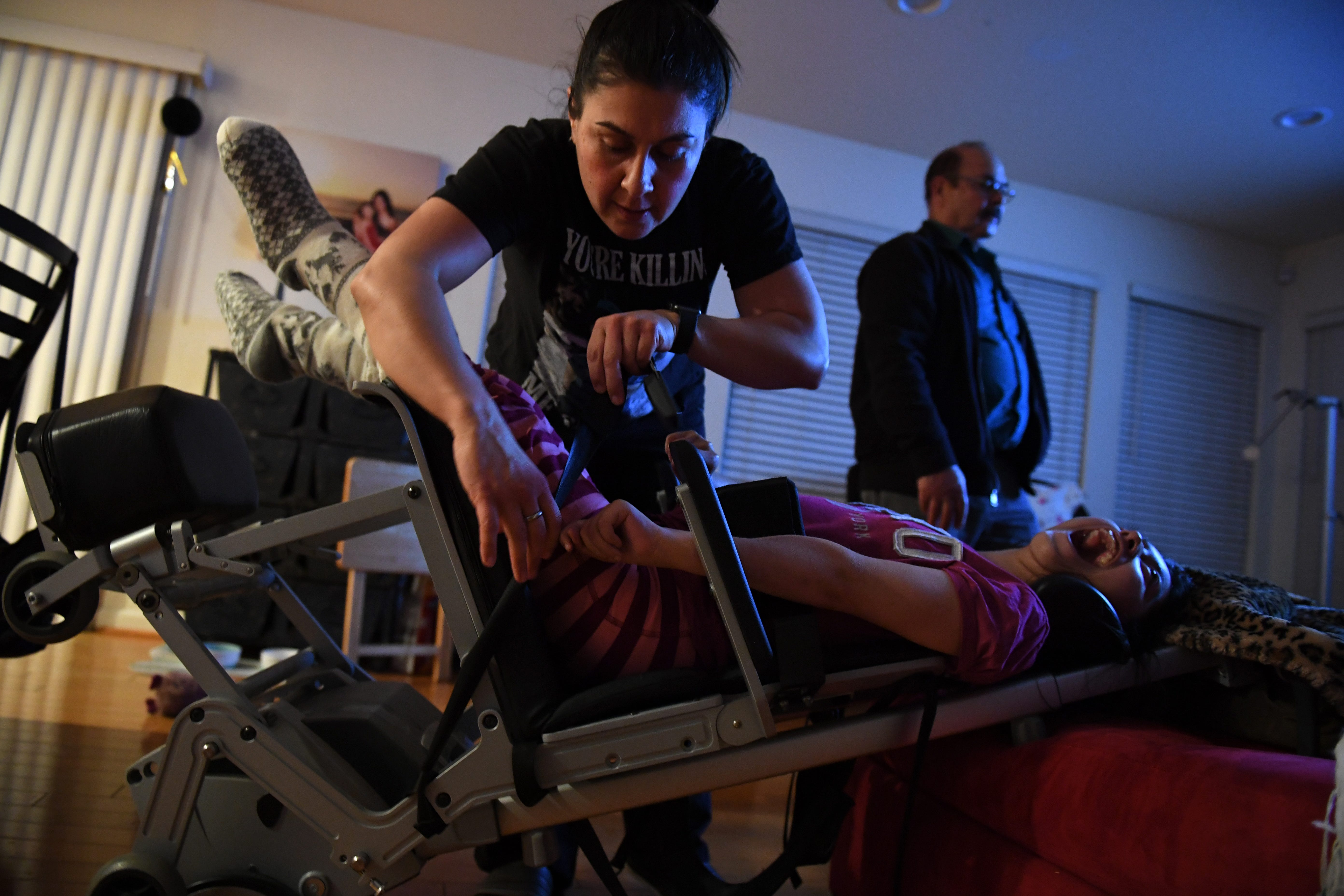 Maribel Landeros straps in her daughter Karizma into her chair one night at her Salinas home. Maribel's father stands behind her as a TV plays.