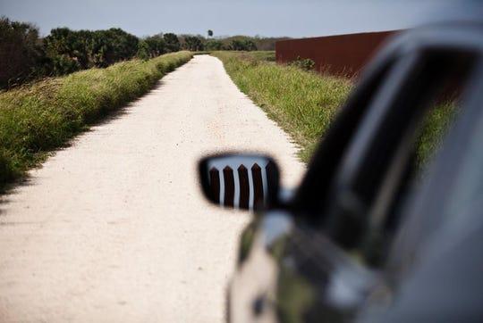 U.S. Customs and Border Patrol agents patrol wide gravel roads along the border fence.