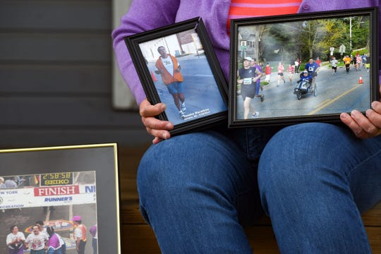 Jan Shafer presents a collection of photos of her father John Jones, running through the years on Wednesday, May 20, on her front porch in Sioux Falls.