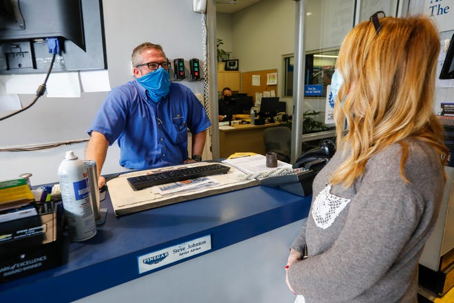 Service Advisor Steve Johnson, left, wears a face mask at Pinegar Chevrolet in Republic, Mo., on Wednesday, May 20, 2020.