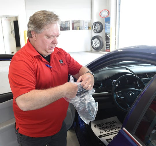 Wade Hartman, who works in the service department at St. Cloud Toyota, prepares a steering wheel cover Wednesday, May 20, 2020, in Waite Park.