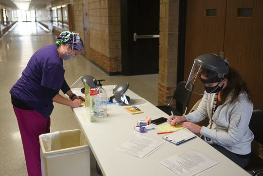 Licensed practical nurses Kaila Current and Tamara Muzik finish up COVID-19 screenings Wednesday, May 20, 2020, at Apollo High School.