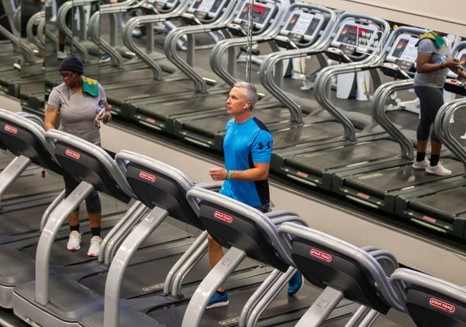 Two people workout on treadmills at Momentum Fitness while they practice social distancing. Every other cardio machine has a sign saying it is temporarily closed so everyone can practice social distancing.