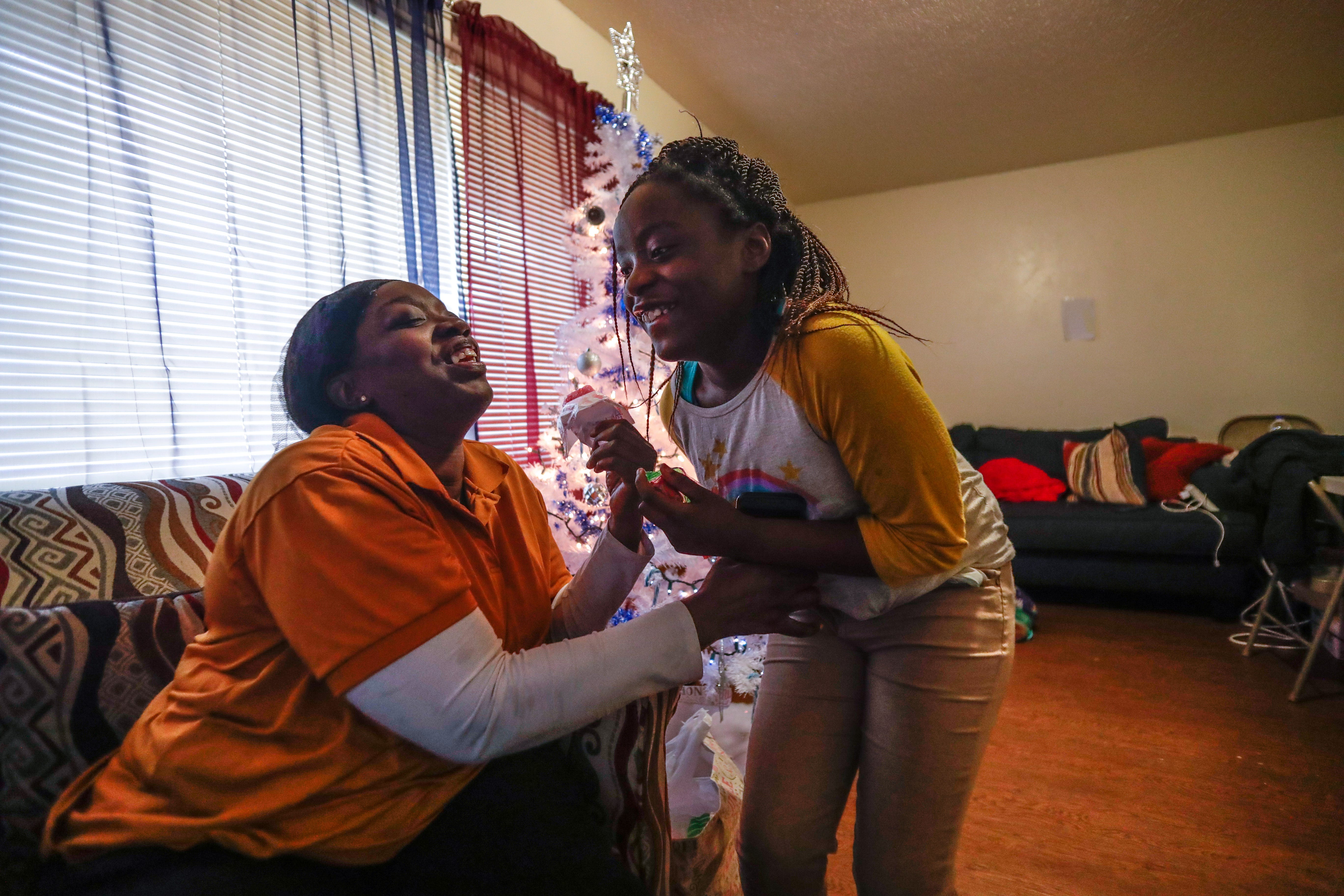 """Kisha Simms, 38, tickles her daughter Deitra """"DeeDee"""" Jackson, 11, as they both have an afternoon snack and catch up on each other's day."""