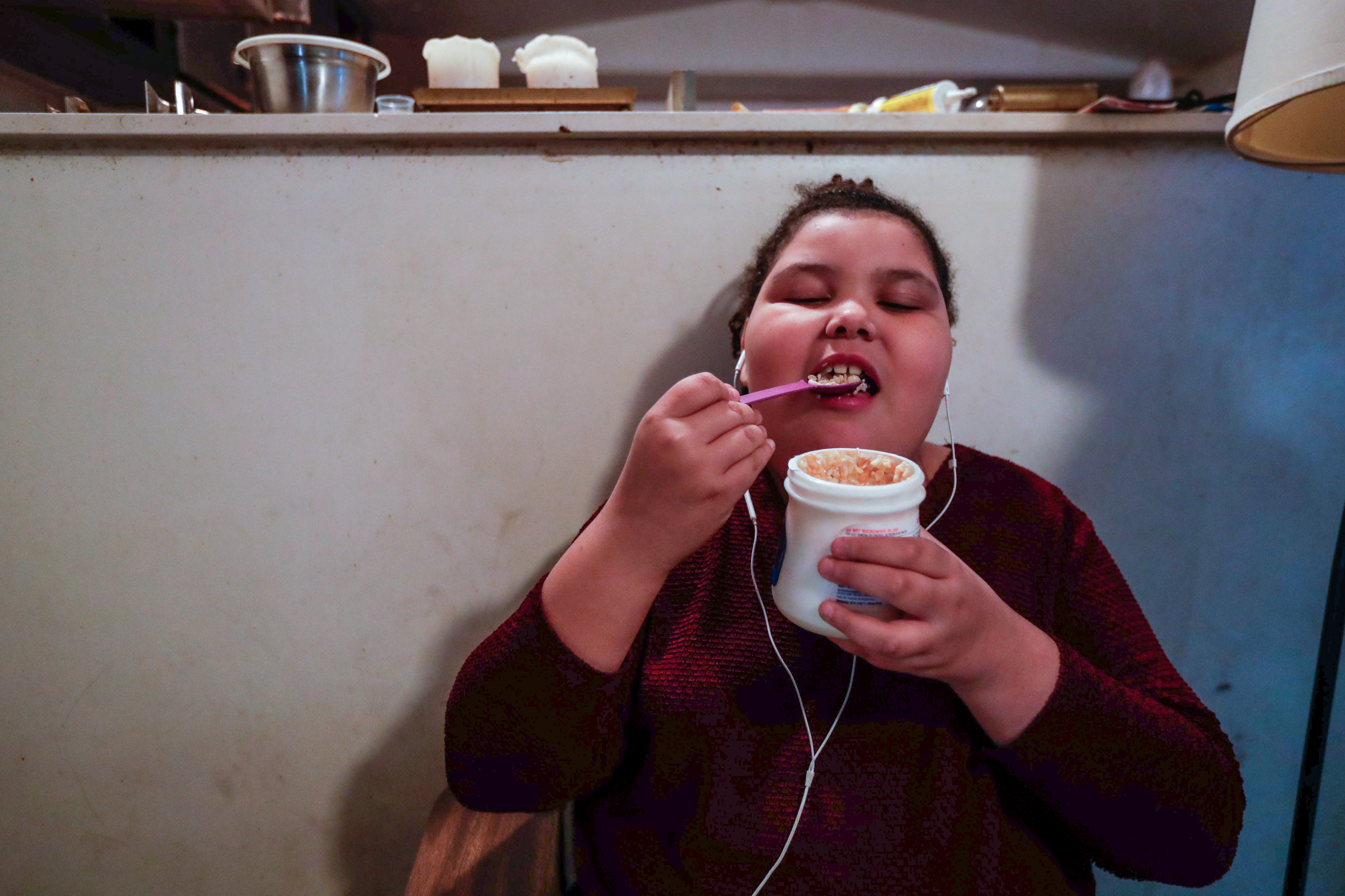 Vivianna Hughes, 9, sits at a school desk in the living room of the family's mobile home while eating marshmallow fluff and Rice Krispies cereal as an afternoon snack. A cockroach scurries along the ledge of the counter above Vivanna's right shoulder.