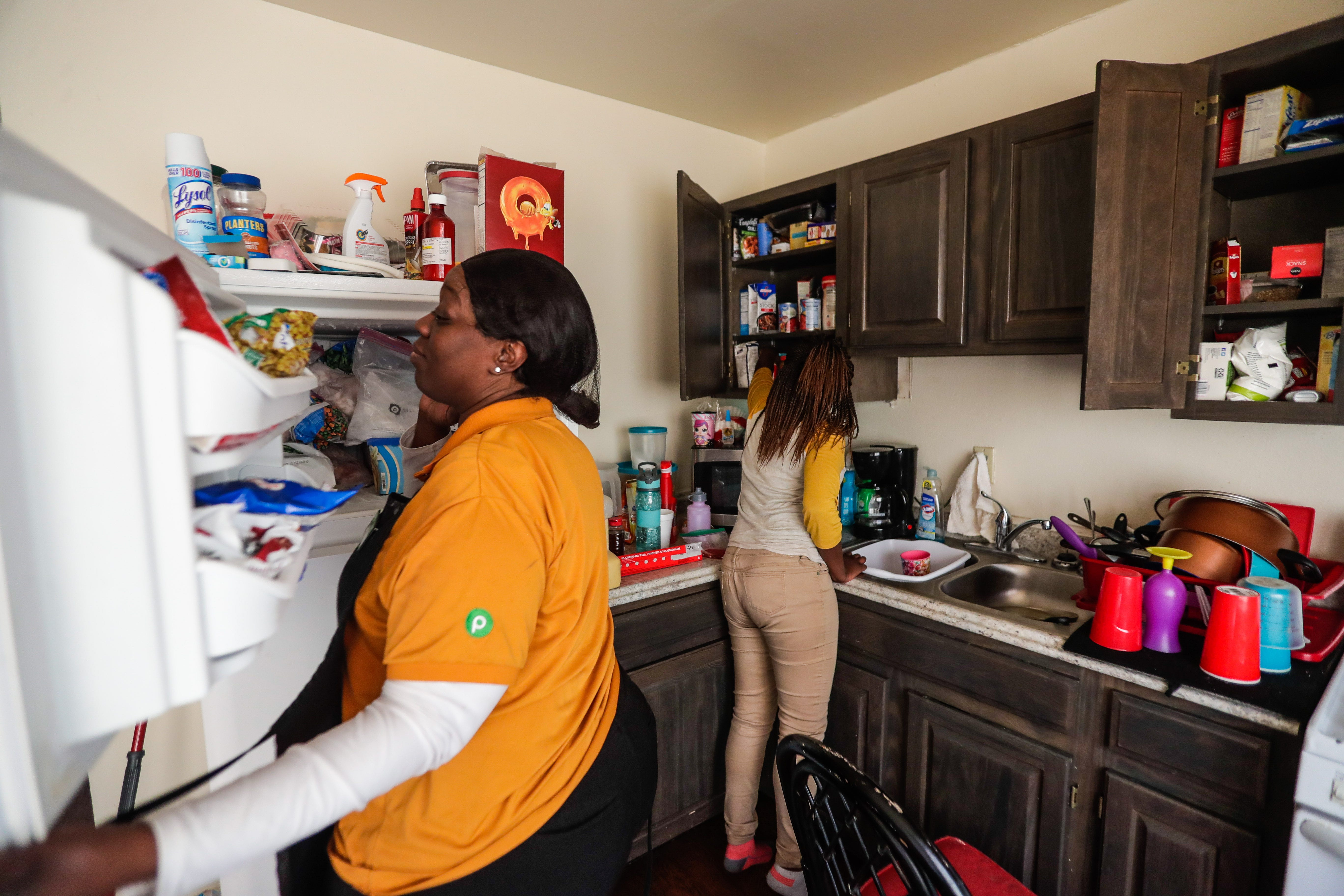 """Kisha Simms, 38, and her daughter Deitra """"DeeDee"""" Jackson, 11, look for afternoon snacks in their kitchen."""