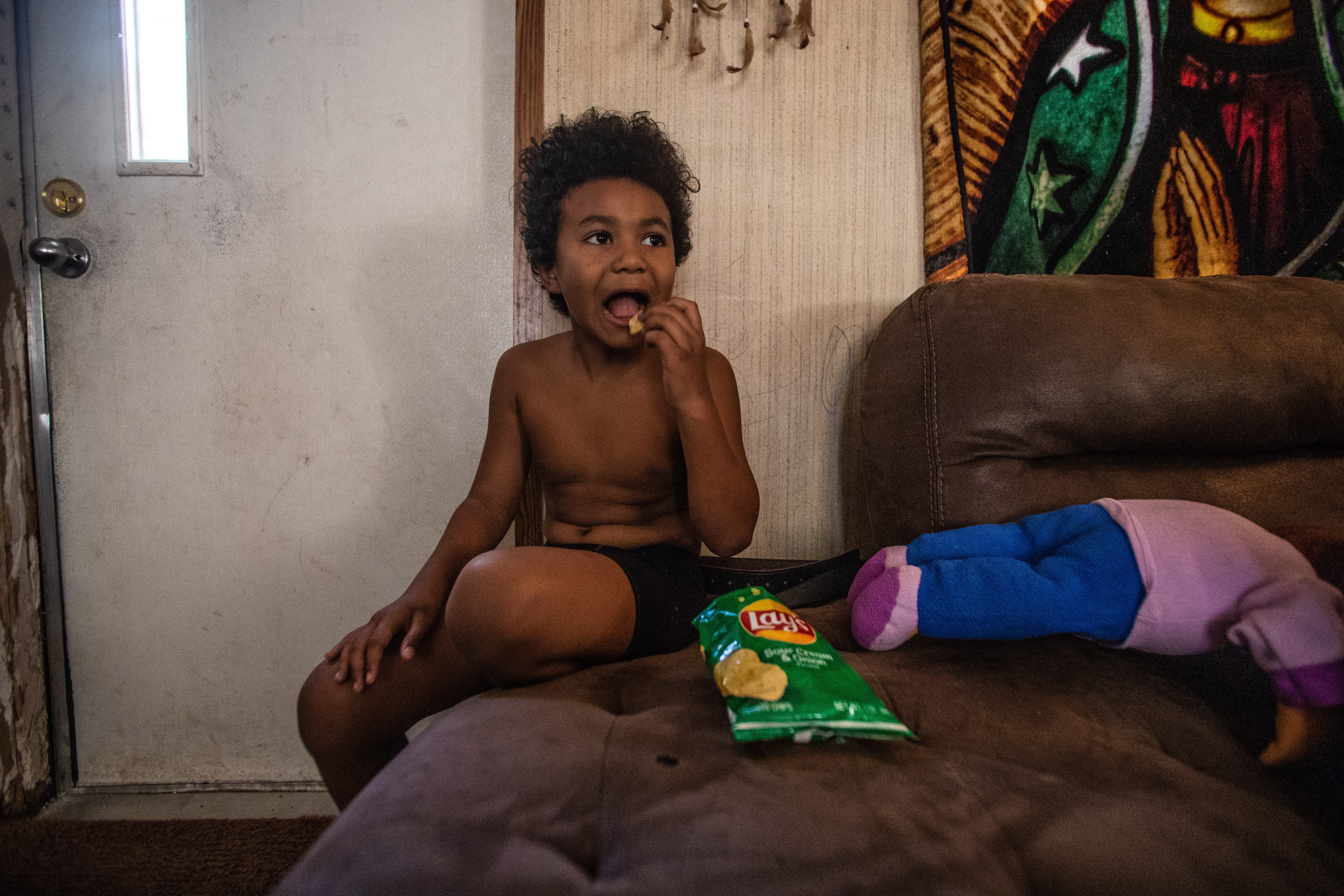 Romeo, 8, eats sour cream-and-onion chips on the living room couch in his mobile home off Aenon Church Road.