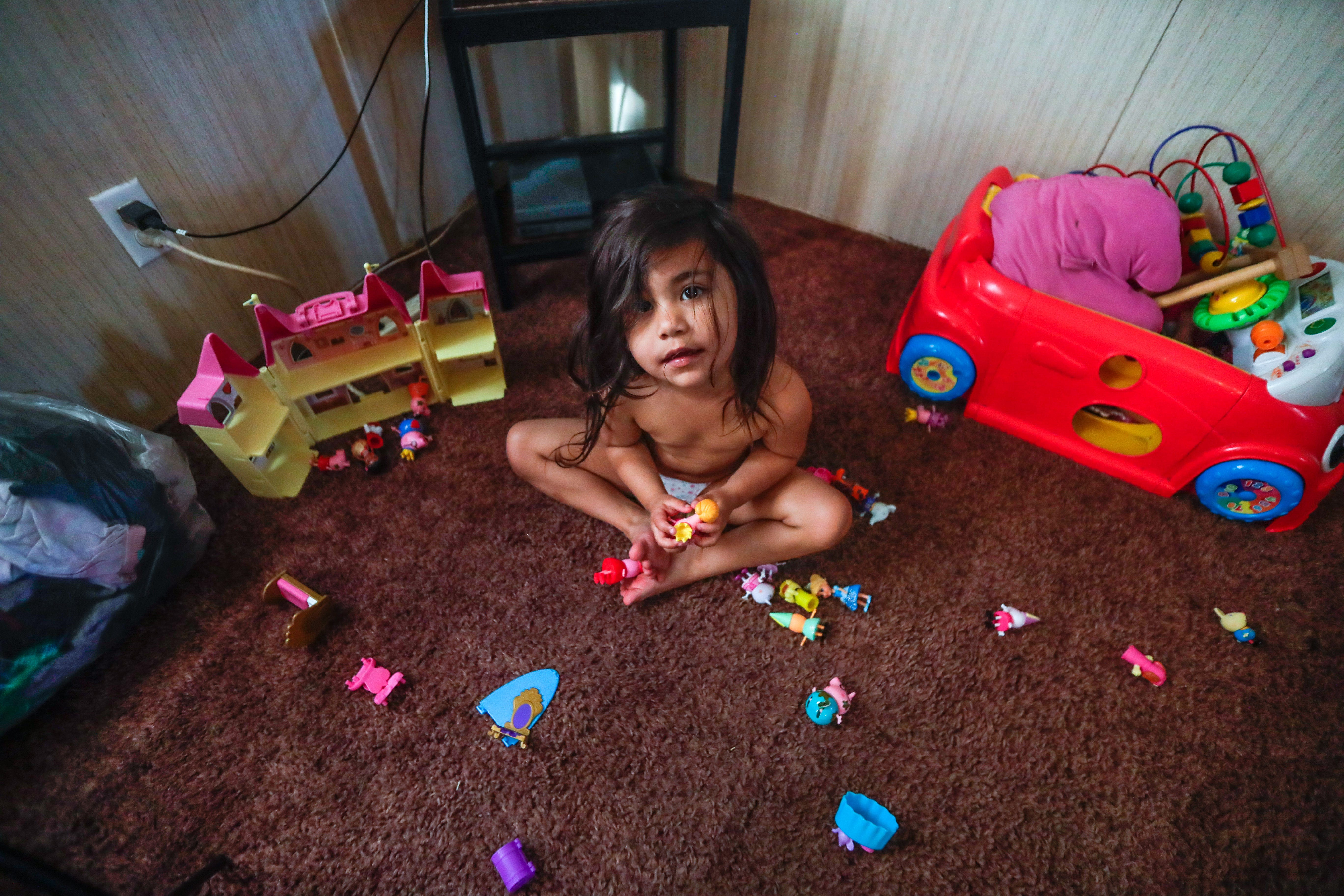Victoria, 3, looks up from her toys on the living room floor of her family's mobile home off Aenon Church Road.