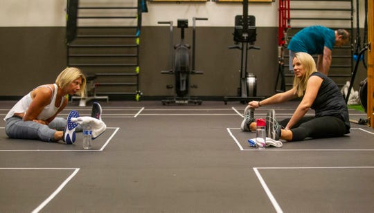Two women stretch before a class at Momentum Fitness. Rectangles created with tape designate a space for individuals to workout in while practicing social distancing.