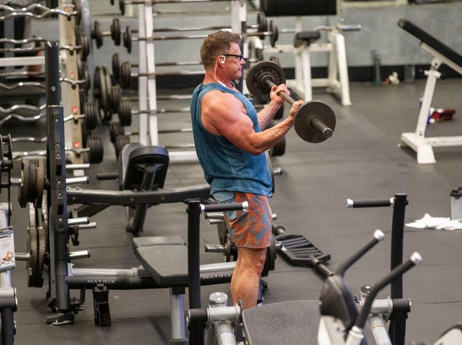A man lifts a barbell as he works out while being socially distant from others at Momentum Fitness.