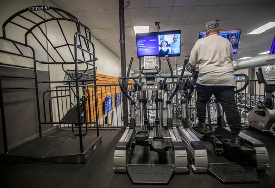 A man works out on an elliptical at Momentum Fitness. Every other cardio machine has a sign saying it is temporarily closed so everyone can practice social distancing.