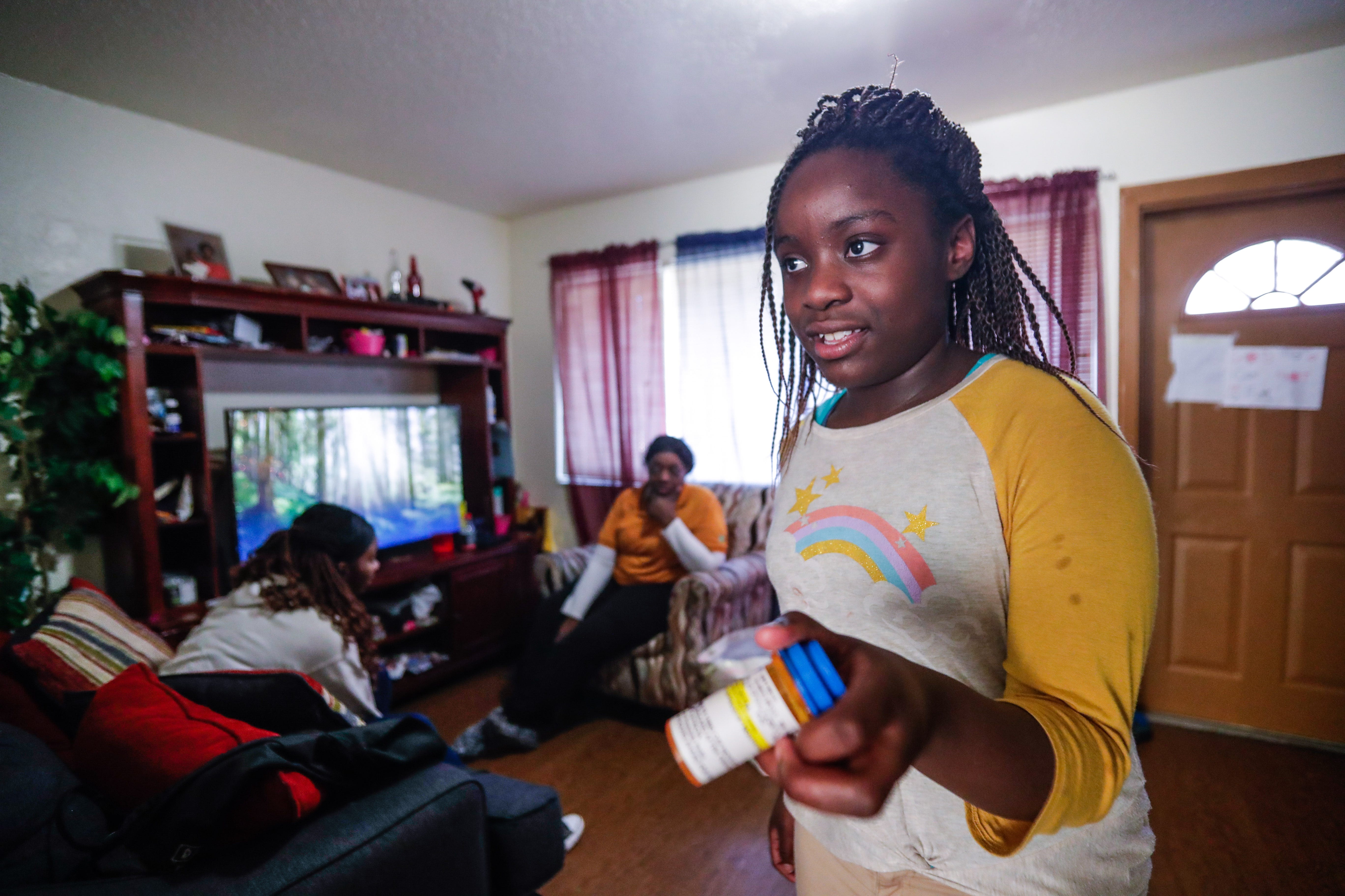 """Deitra """"DeeDee"""" Jackson, 11, shows what her prescription is that helps with her ADD. Both DeeDee and her older sister Lynaya Saylor, 18, have ADD."""
