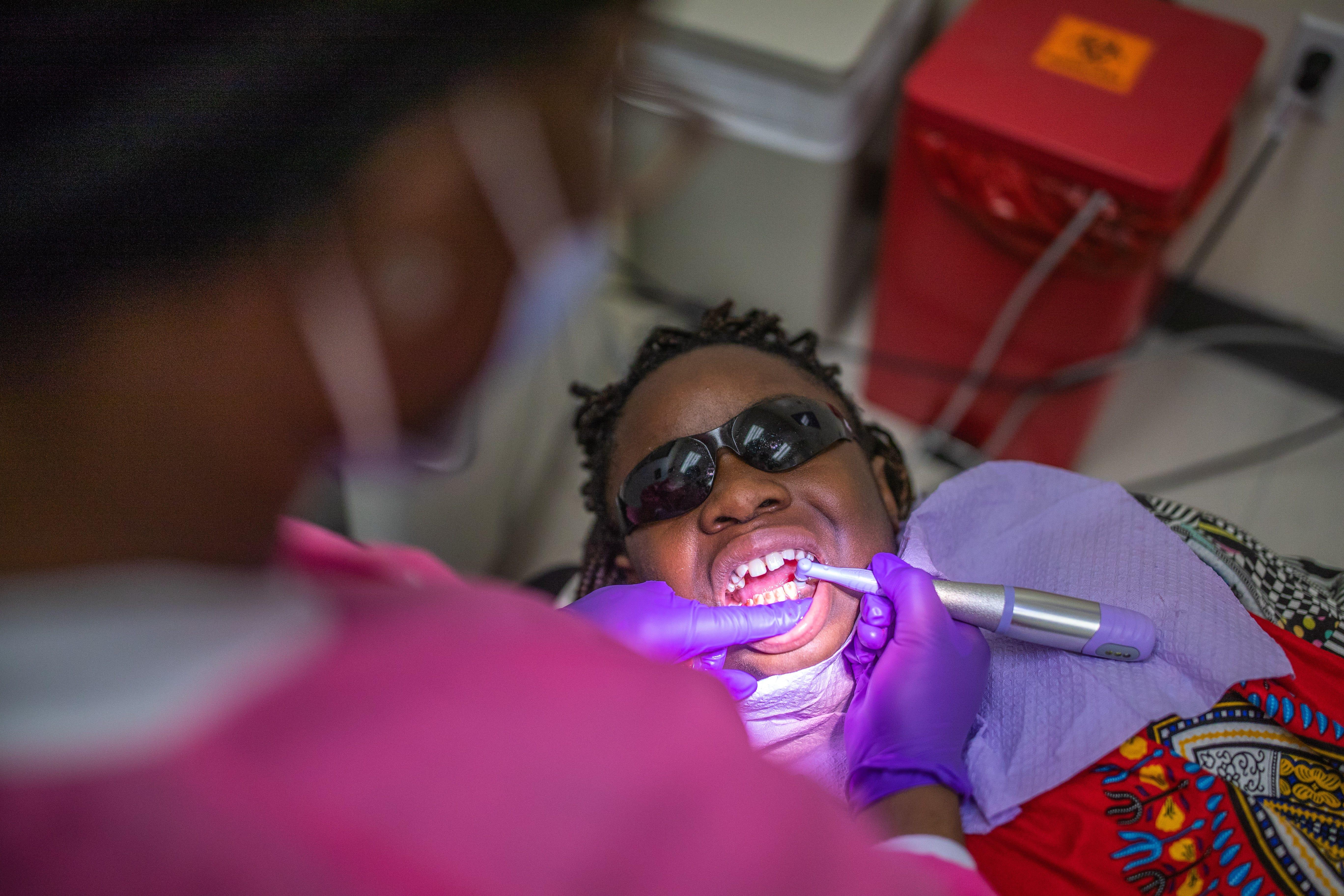 "A dental hygienist cleans 11-year-old Deitra ""DeeDee"" Jackson's teeth at Neighborhood Medical Center."
