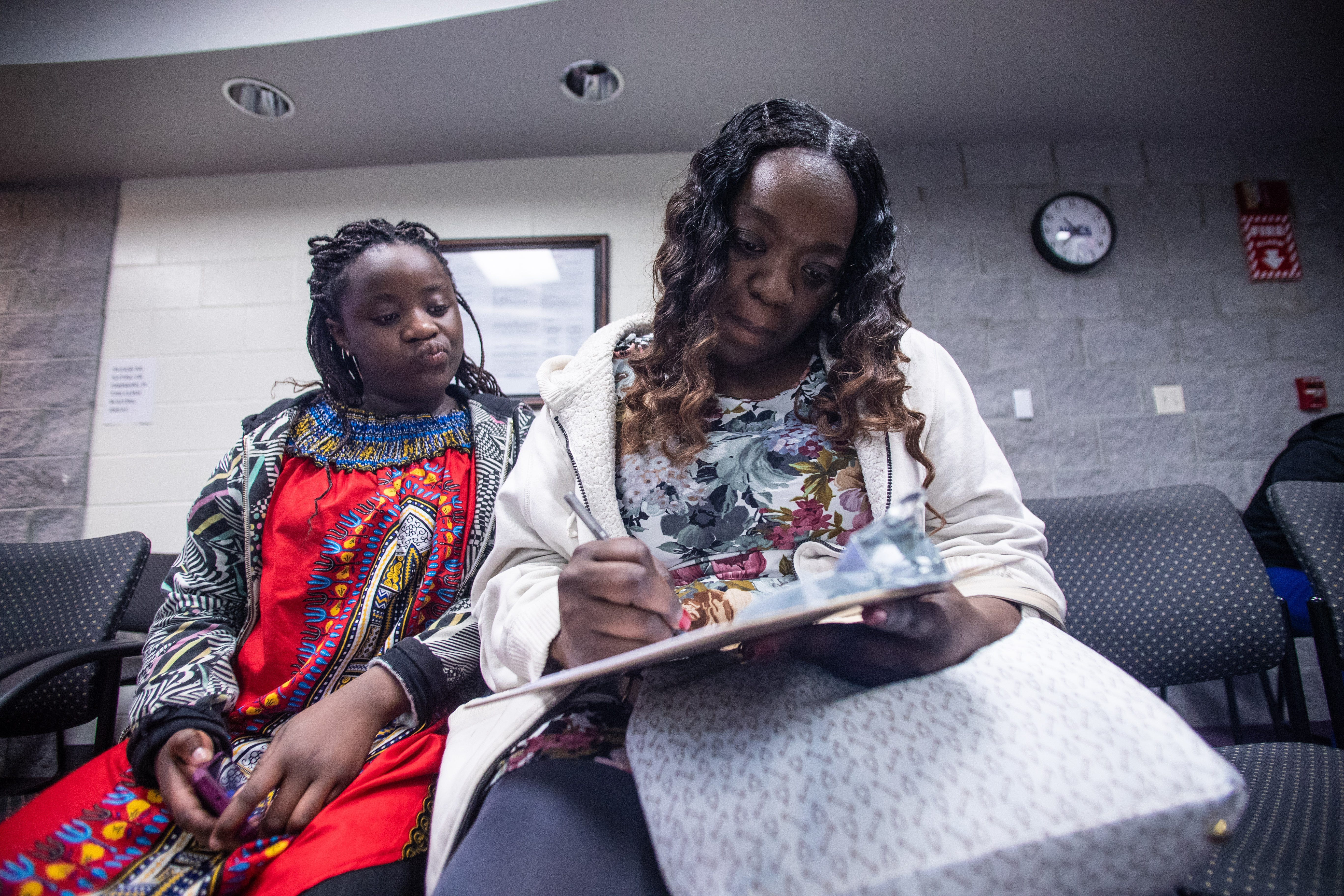 """Kisha Simms, 38, fills out paperwork before a dentist appointment for her 11-year-old daughter Deitra """"DeeDee"""" Jackson at Neighborhood Medical Center."""