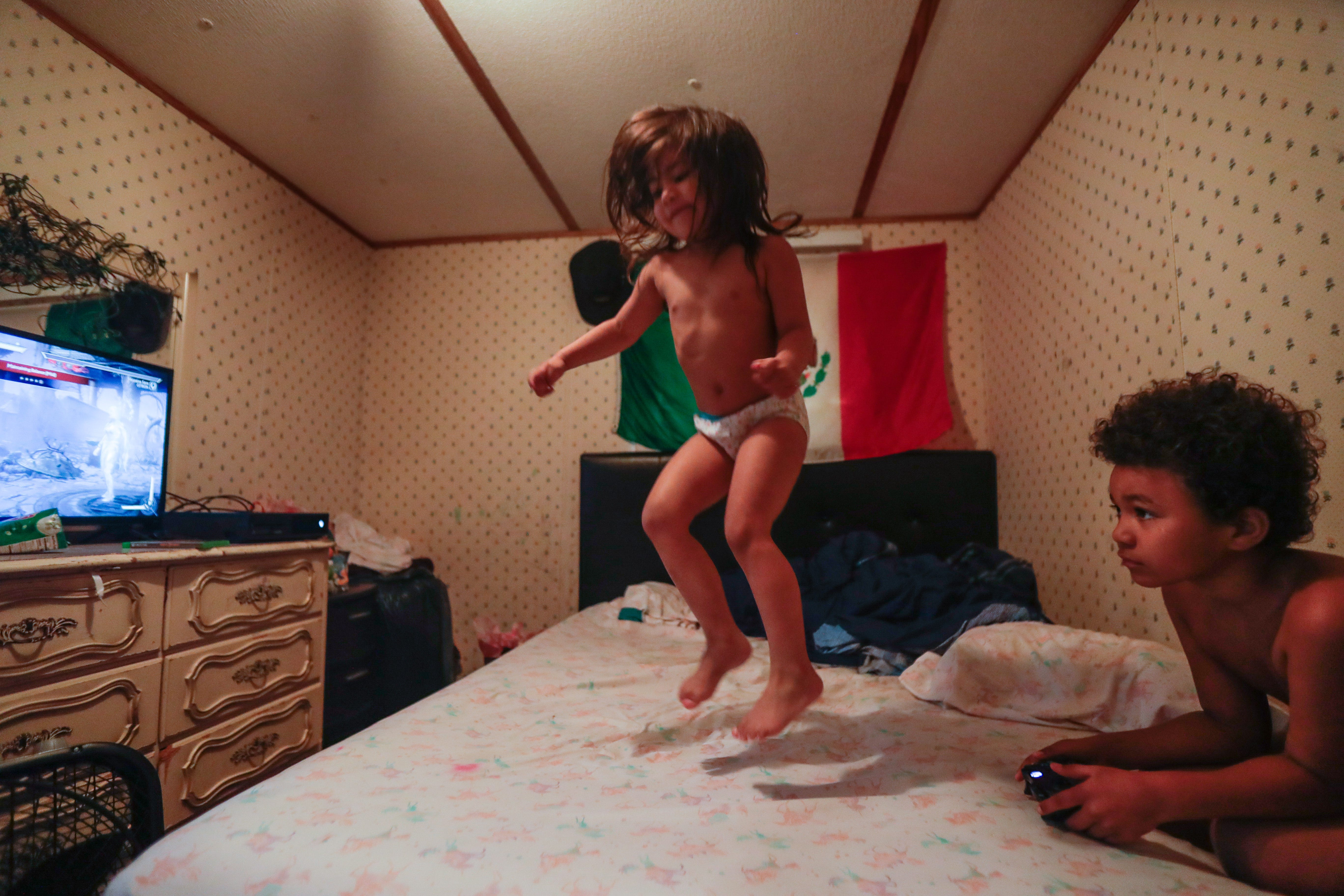 Victoria, 3, jumps on her mom's bed while her 8-year-old brother Romeo plays Xbox games. The siblings live with their mom, her younger sister, and their mom's husband.