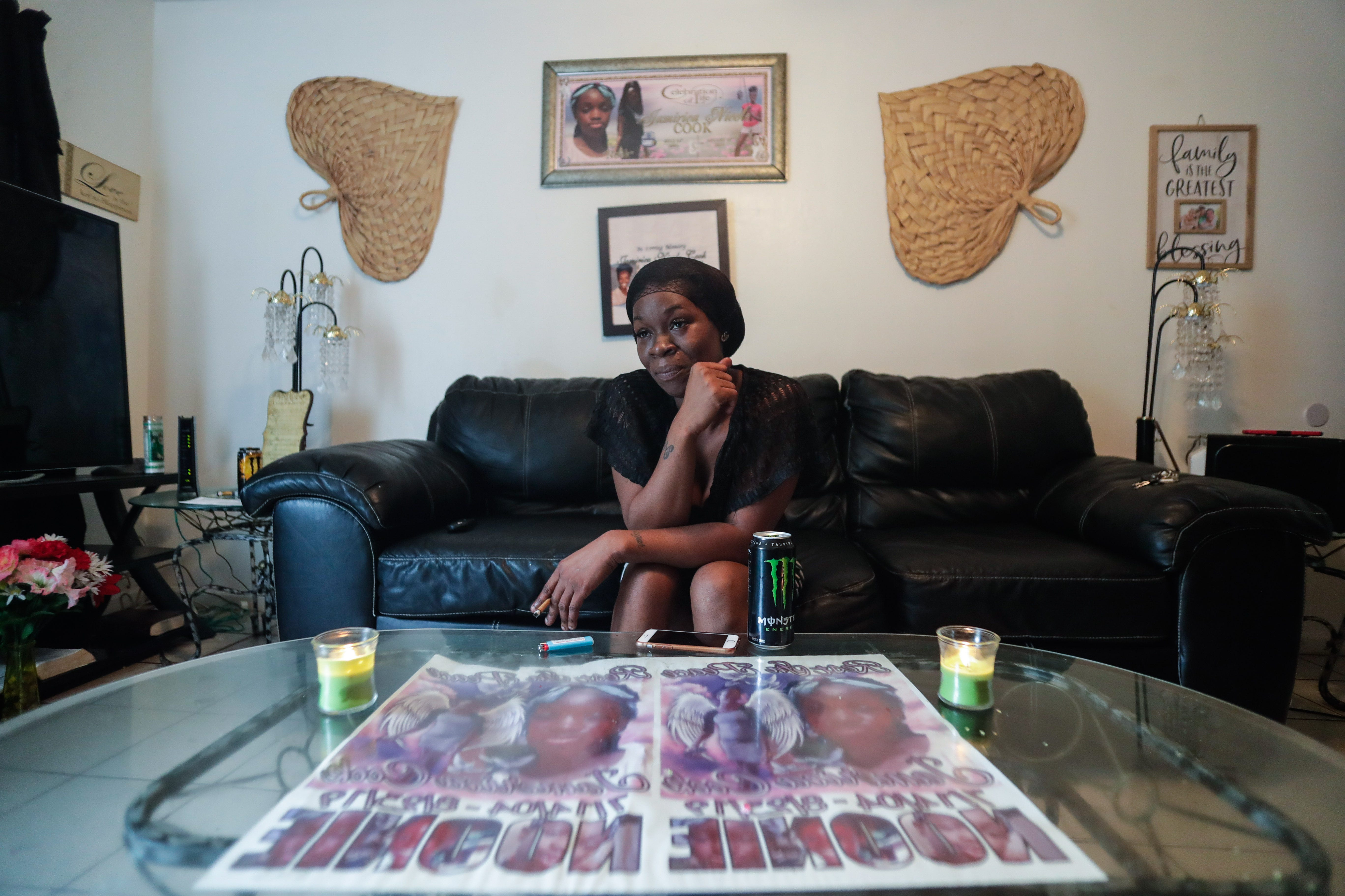 """Koquisha Cook, 36, sits in her living room as she shares fond memories of her daughter Jamirica """"Noonie"""" Cook, 15, who was shot and killed last year in her home in the Springfield Apartment complex. Photographs and tributes to Noonie decorate Cook's home."""