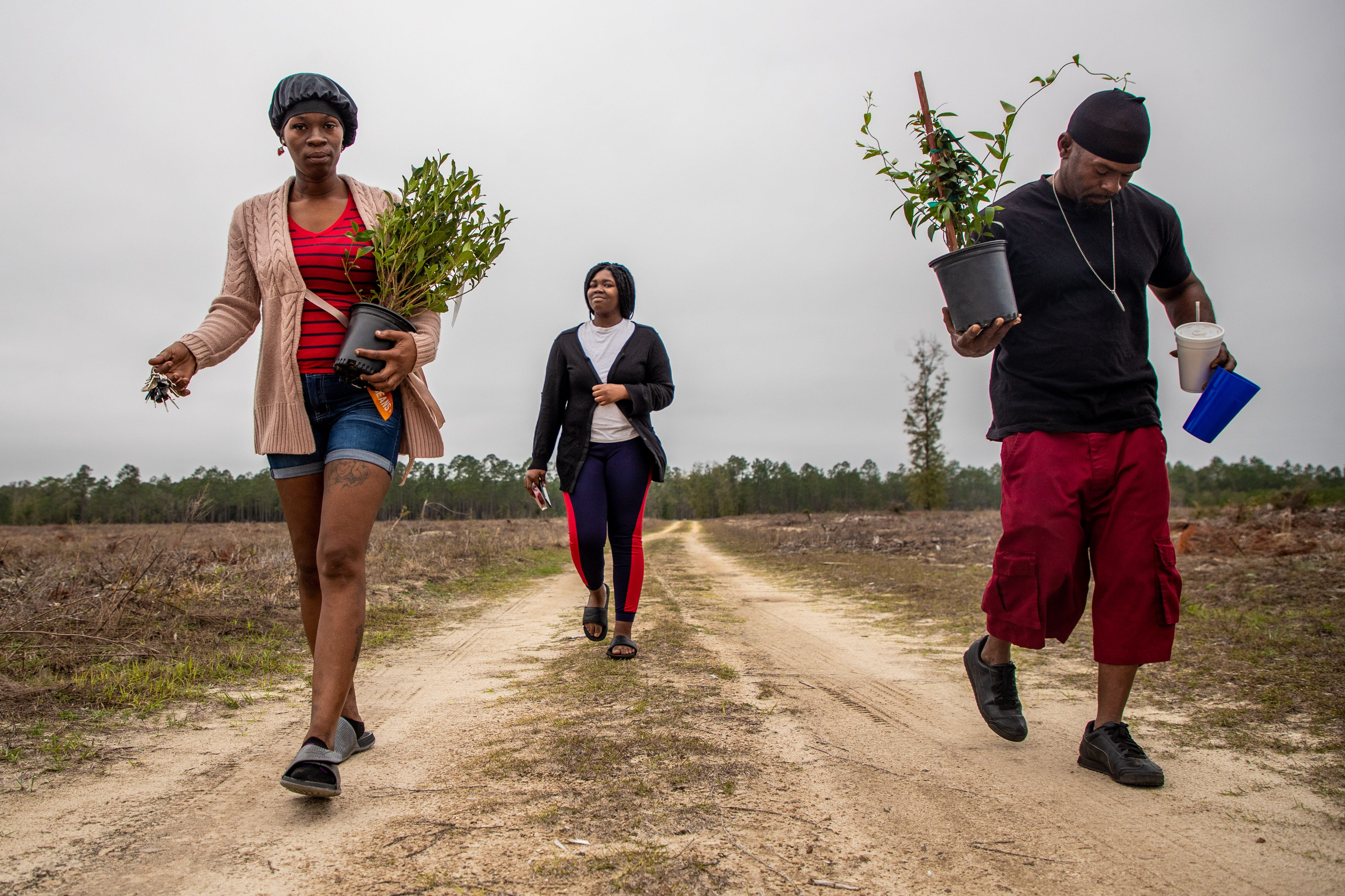 """Koquisha Cook, 35, left, and her boyfriend Kevin Moore carry plants as they walk to Noonie's gravesite. Jamirica """"Noonie"""" Cook, 15, was shot and killed last year in her home at Springfield Apartments. Noonie's sister Sharail """"Sugar"""" Sampson, 14, carries a heart-shaped box of chocolates to leave on her sister's grave."""