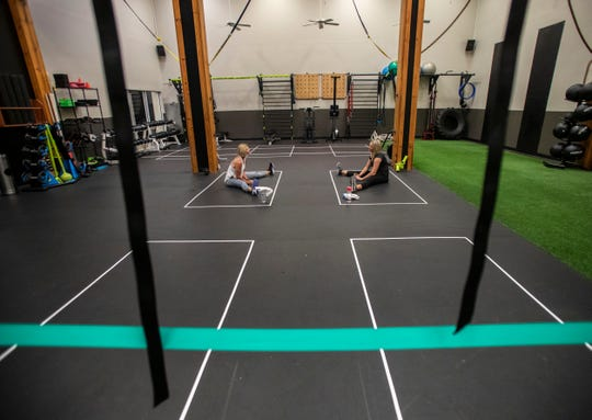 Rectangles created from tape designate workout spaces for individuals during group classes at Momentum Fitness.