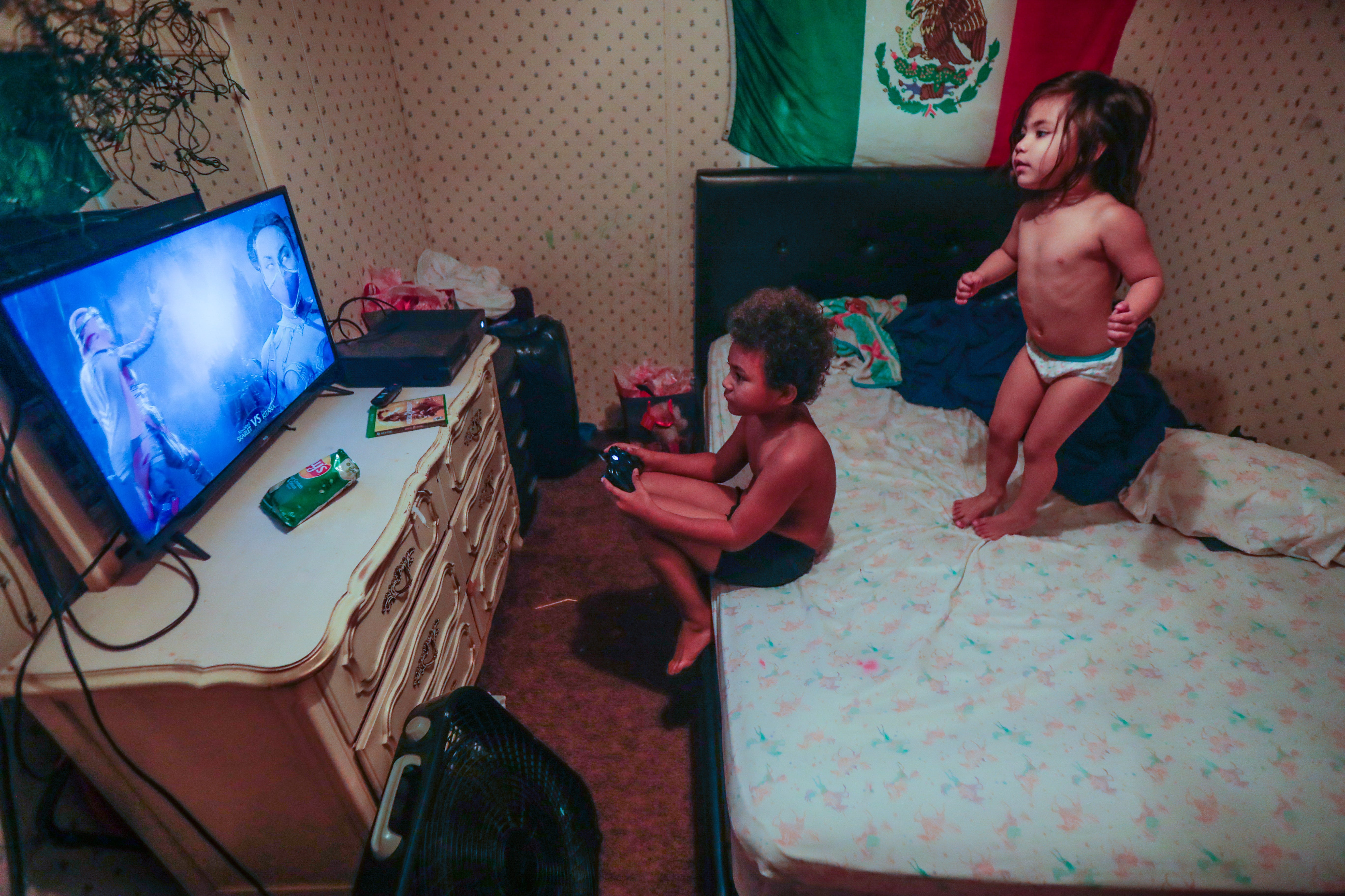 Victoria, 3, jumps on her mom's bed while her brother Romeo, 8, plays video games on his Xbox. The siblings live with their mom, her younger sister, and their mom's husband.