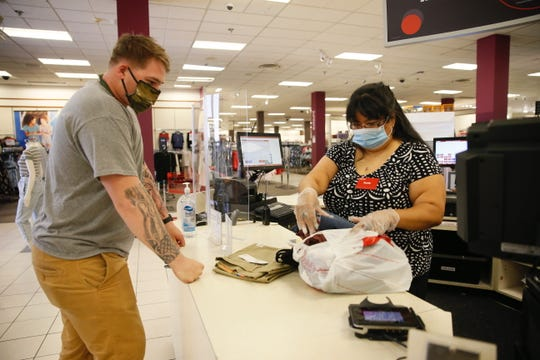 Sandy Molina, pricing and sales associate, rings up an online order for Matthew Fowler on Wednesday, May 20, 2020, at the J.C. Penney store at Cielo Vista Mall in El Paso.