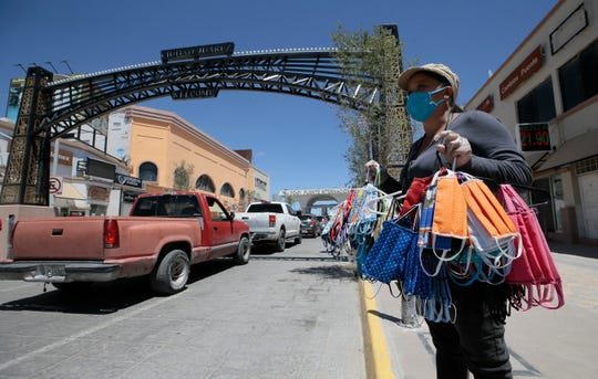 Elizabeth Martinez sells homemade coronavirus masks along Avenida Juárez to commuters crossing the Paso del Norte International Bridge Thursday, May, 20, 2020.