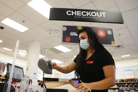 Sales associate Marisol Chavira rings up a customer Wednesday, May 20, 2020, at the J.C. Penney store at Cielo Vista Mall in El Paso.
