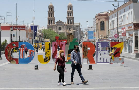 Juárenses stroll through the city center wearing masks to protect themselves from coronavirus.