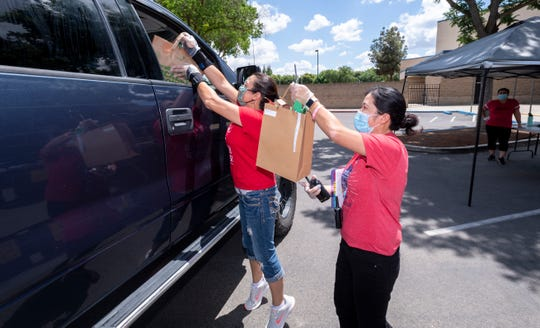 Assistant principal Bo Yang, right, teacher Sara Rocha and other Hurley Elementary School staff began distributing the belongings of more than 600 students Tuesday, May 19, 2020. The week is also a chance to return items like library books and musical instruments.