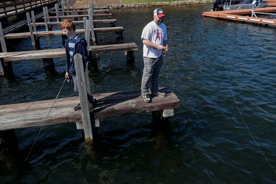 Blake Waldinger, 14, and his father, Brett, fish on Wednesday from a dock on Minocqua Lake in Minocqua.