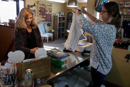 Sandra Lowe, left, pays for her items while Emma Berlyn bags them on May 19 at Sweet Tea Clothing Co. in Wisconsin Rapids.