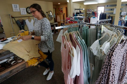 Emma Berlyn restocks items on May 19 at Sweet Tea Clothing Co. in Wisconsin Rapids. The shop reopened after safer-at-home restrictions on small businesses were partially lifted on March 11.