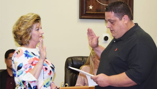 Gaylynn Burris takes the mayor's oath administered by Mayor Pro Tem Jason Love during a recent council meeting.
