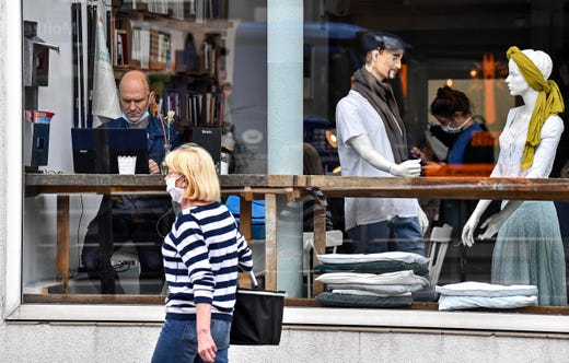 A customer sits with his laptop beside display mannequins at the Cafe Livres in Essen, Germany, May 20, 2020. The cafe set the dolls as placeholders on various places for more distance between customers due to the new coronavirus orders for restaurants and cafes.