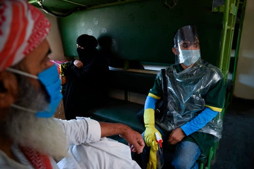 A passenger wearing a face shield sits along with others in a train carriage of Karachi bound Awam Express at the Rawalpindi railway station as train services resumed ahead of the Muslim Eid al-Fitr festival after the government eased a nationwide lockdown imposed as a preventive measure against the COVID-19 coronavirus, in Rawalpindi on May 20, 2020.