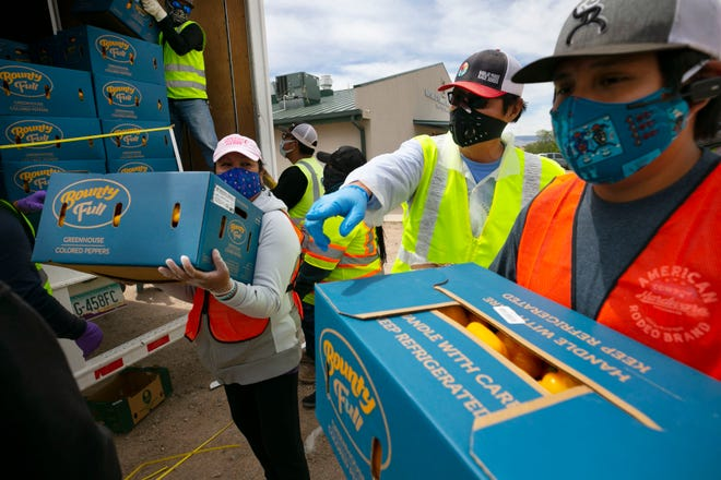 Navajo Nation President Jonathan Nez, center, and Isaiah Tsosie, right, an office specialist with the Coyote Canyon chapter, move fresh food off a truck to be distributed to community members at a food distribution point before the start of a weekend long curfew, in Coyote Canyon, N.M., on the Navajo Nation on May 15, 2020. All businesses including the 13 grocery stores on the reservation were closed during the weekend long curfew to combat the new coronavirus pandemic. The Navajo Nation has been one of the hardest hit areas from the COVID-19 pandemic in the entire United States.