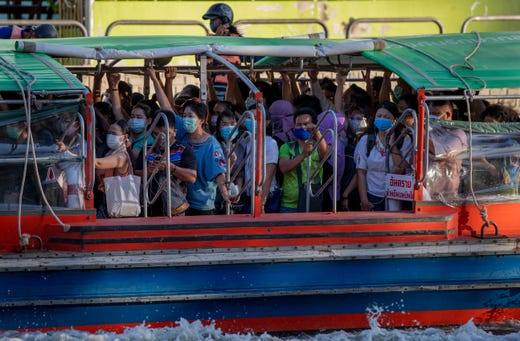 Passengers wearing face masks stand in close proximity as they ride a canal boat during the evening rush hour in Bangkok, Thailand, May 20, 2020. The Thai government continues to ease restrictions related to running businesses in the capital Bangkok that were imposed weeks ago to combat the spread of COVID-19.