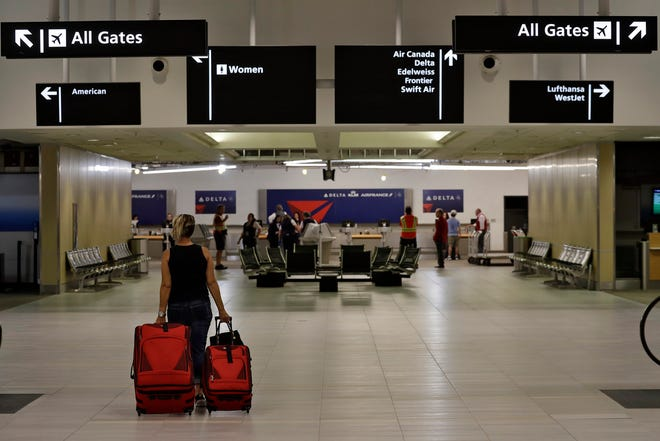 A passenger carries her luggage through a nearly deserted terminal at the Tampa International Airport on April 24, 2020, in Tampa, Fla. Business at the airport has been at a near standstill due to the coronavirus outbreak.