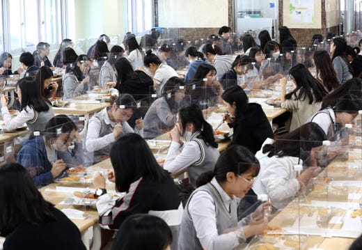 Students sit behind protective screens as a preventative measure against the COVID-19 novel coronavirus as they eat lunch at a high school in Daejeon on May 20, 2020.  Hundreds of thousands of South Korean students returned to school on May 20 as education establishments started reopening after a coronavirus delay of more than two months.