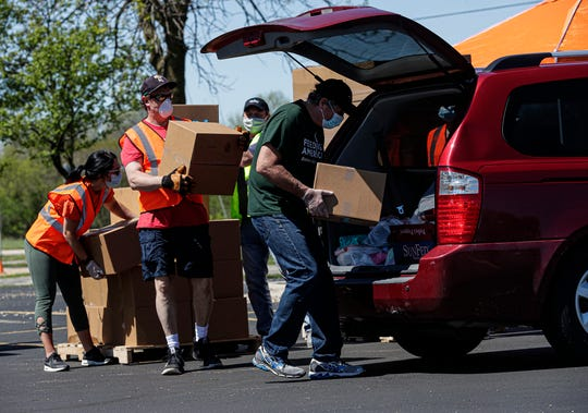 Volunteers with Feeding America Eastern Wisconsin load boxes of food into vehicles Thursday, May 21, 2020 at Nathan Calder Stadium in Menasha. The food is for those needing help during the coronavirus pandemic. Doug Raflik/USA Today NETWORK-Wisconsin