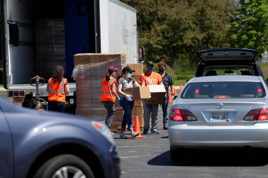 Volunteers with Feeding America Eastern Wisconsin load boxes of food into vehicles Thursday, May 21, 2020 in Oshkosh, Wis. The food is for those needing help during the coronavirus pandemic. Doug Raflik/USA Today NETWORK-Wisconsin