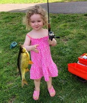 Nora Rose Davis, 3 of Freehold Township, with her first fish which she caught at a pond in Colts Neck