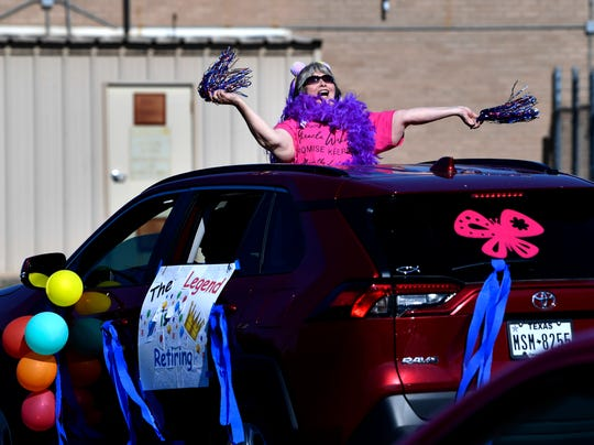 Denise Rister waves her pom-poms in the air to signal the line of nearly 30 vehicles behind her Thursday honoring Georgiana Reagan with a parade.
