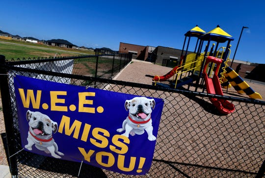 A banner hangs outside an empty playground at Wylie East Elementary School on May 21.